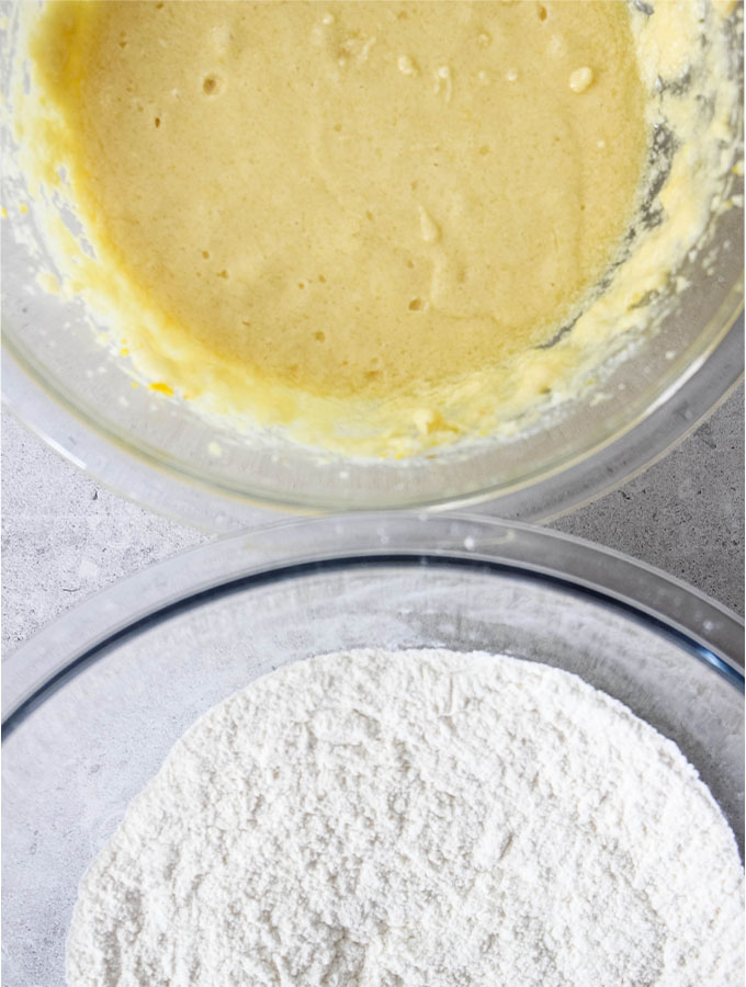 The wet and dry ingredients are stirred in separate bowls to make the Orange Pistachio Biscottis.