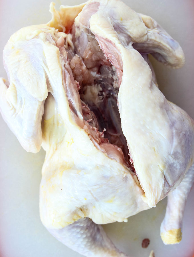 A whole chicken is spatchcocked to make Peruvian Spatchcock Chicken with Aji Verde Sauce.