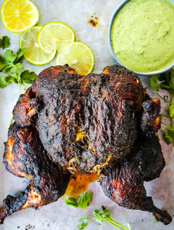 Peruvian Spatchcock Chicken with Aji Verde Sauce is plated with sauce, limes, and more cilantro.