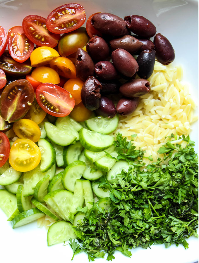 Italian Lemon Orzo Salad ingredients are grouped separately in a white bowl.