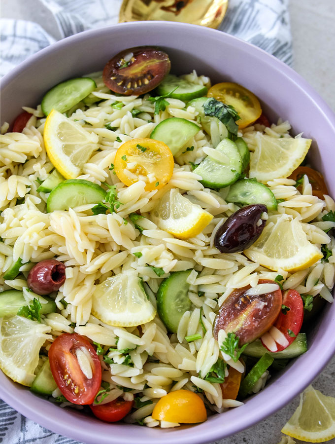 Italian Lemon Orzo Salad is plated in a purple bowl and topped with lemon wedges.