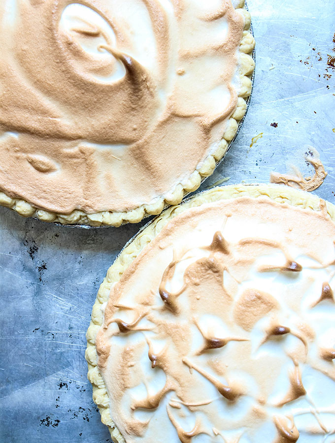 Two key lime pies are on a baking sheet full cooked.