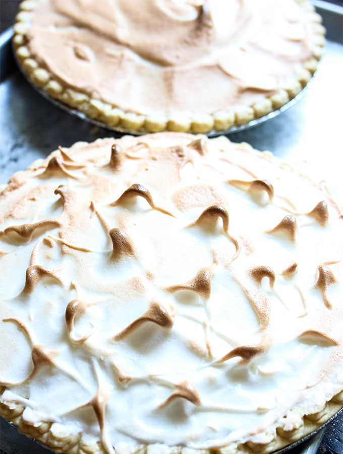 Two key lime pies are on a baking sheet right out of the oven.