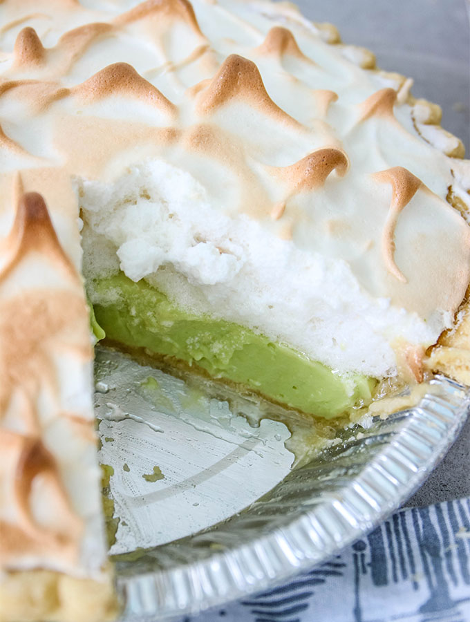 A spiked meringue key lime pie has a slice sliced out of the pie.