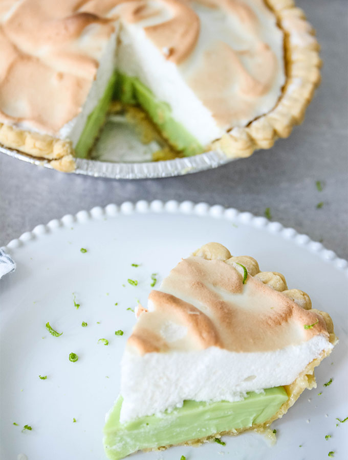 A slice of key lime pie is plated on a white plate next to the whole pie.