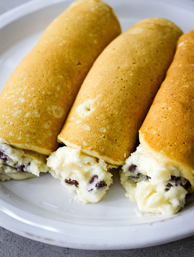 Buttermilk pancakes are stuffed with cannoli filling and plated.