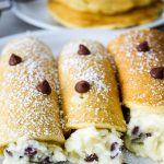 Cannoli stuffed buttermilk pancakes are topped with powdered sugar and chocolate chips.