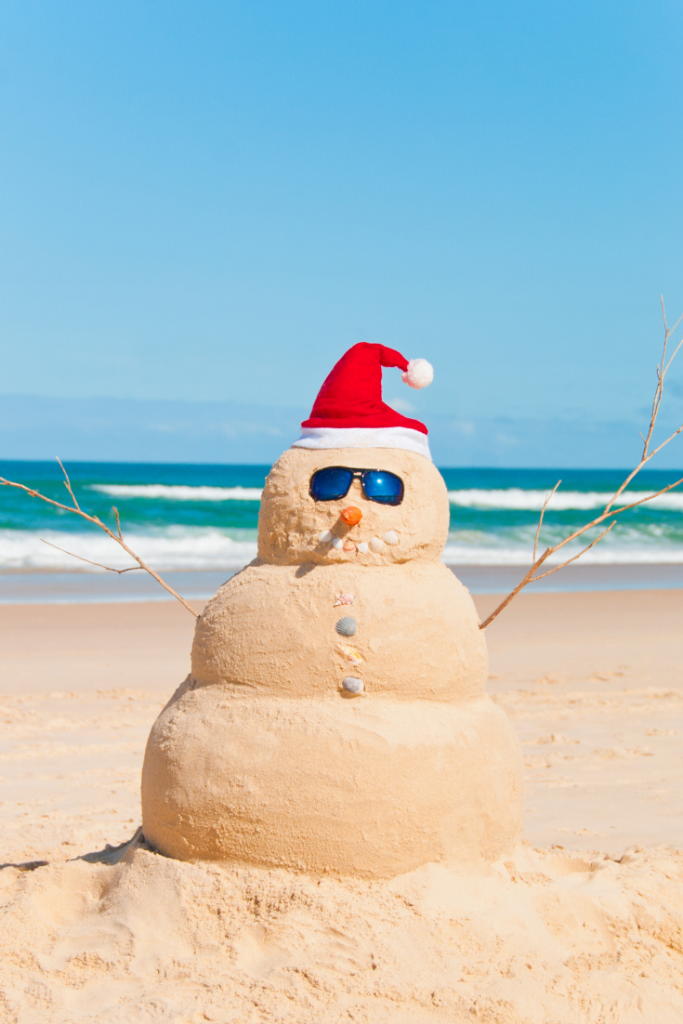 A snowman is made of sand and topped with a Santa hat.