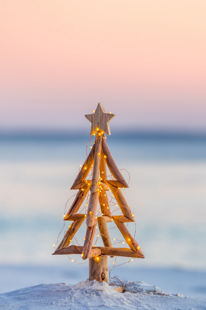 A Christmas tree is strung with fairy lights and placed in the sand.