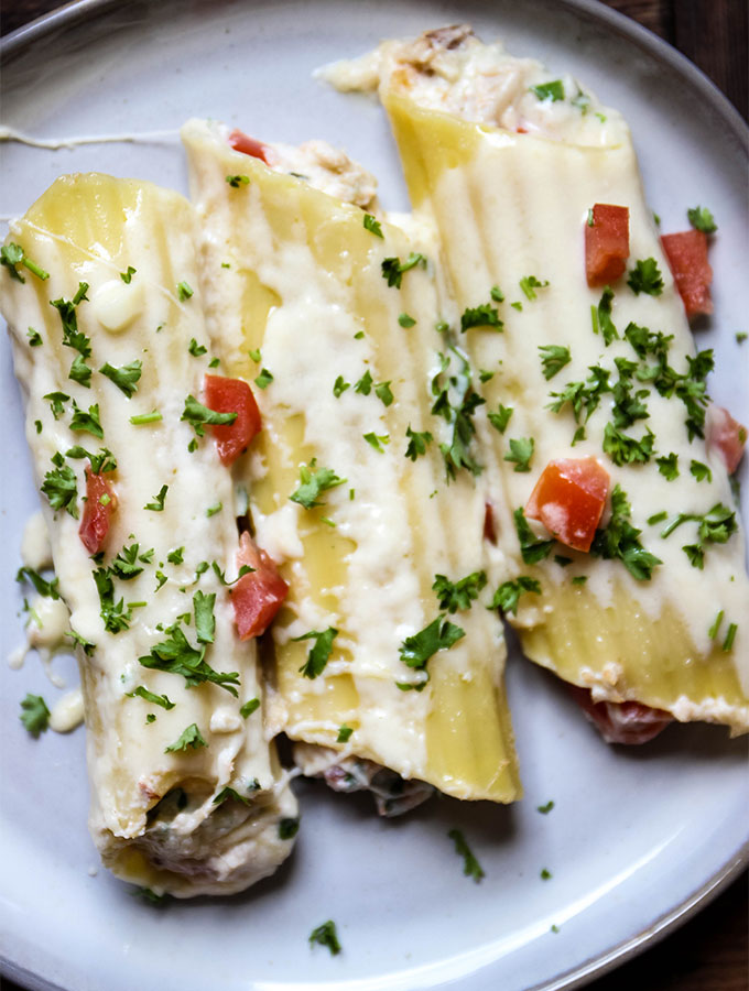Crab Stuffed Manicotti with Alfredo Sauce is plated on a white plate and topped with parsley.