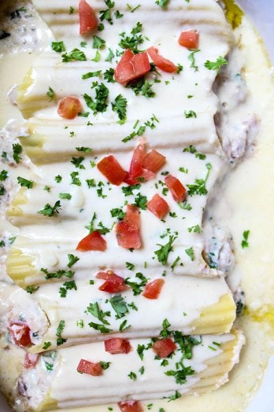 Crab Stuffed Manicotti with Alfredo Sauce is baked, then topped with tomatoes and parsley
