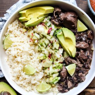 Frijol con Puerco (Mexican Pork and Beans) is plated in a white bowl with avocado slices.