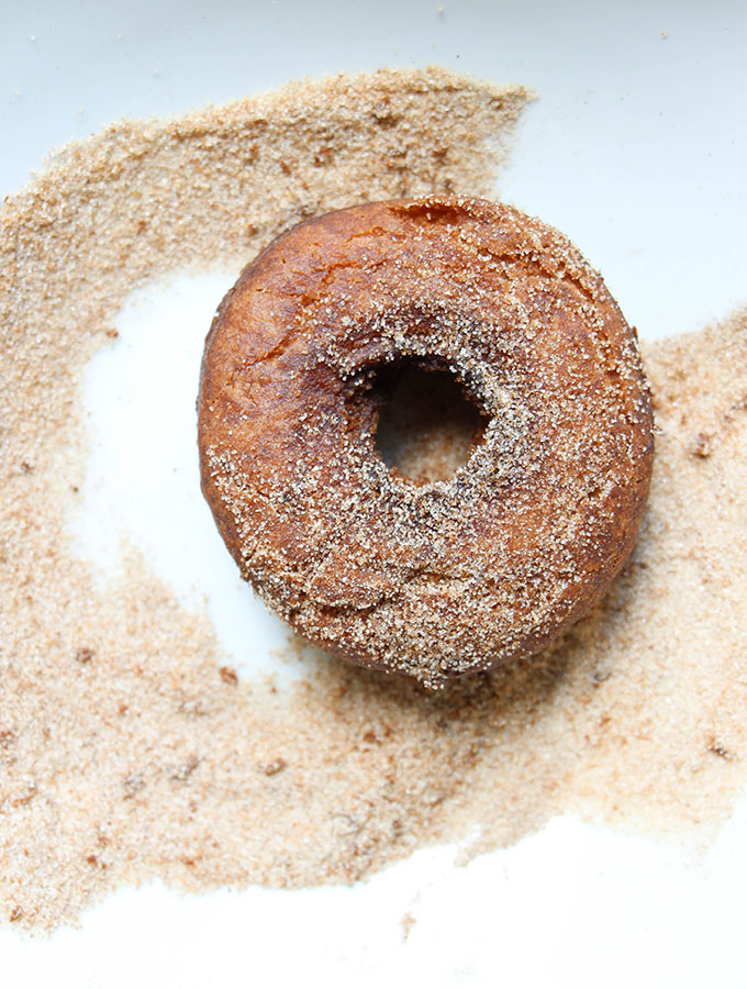 Apple cider donuts are coated in cinnamon sugar in a small bowl.