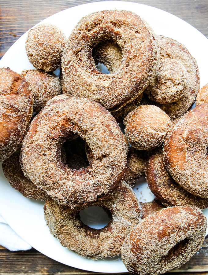 Apple cider donuts are coated in cinnamon sugar on a white plate.
