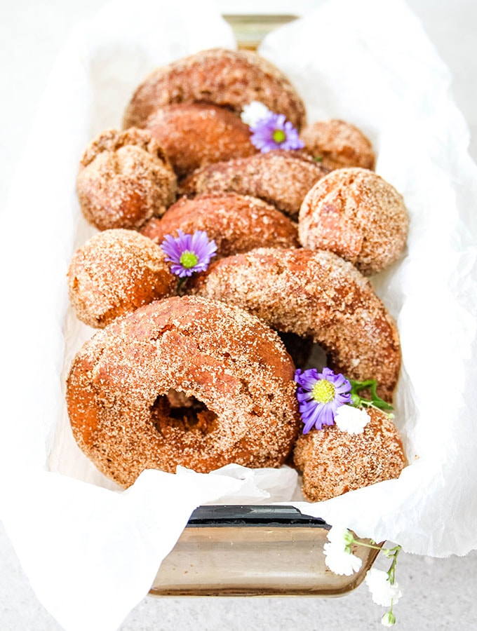 Apple cider donuts are lined in a bowl and topped with fresh flowers.