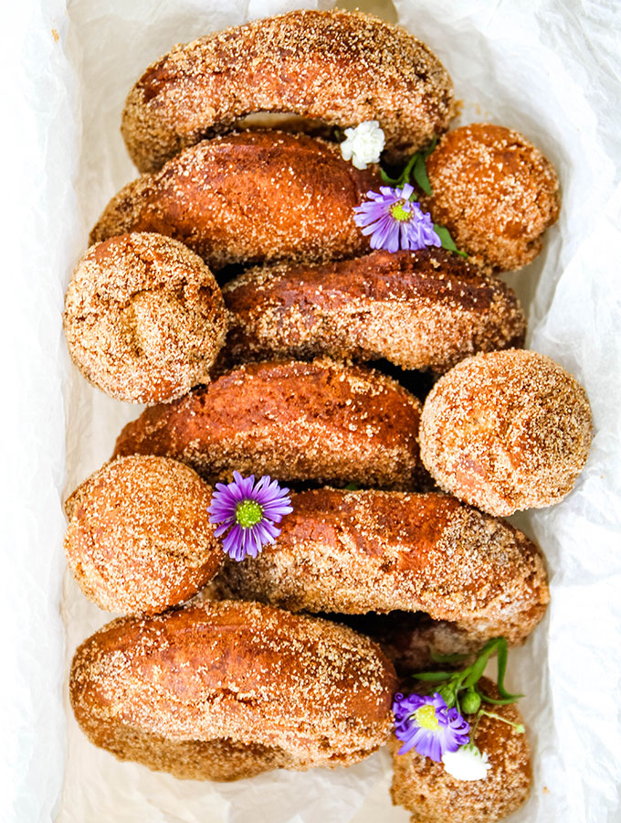 Cider donuts are plated and topped with fresh flowers.