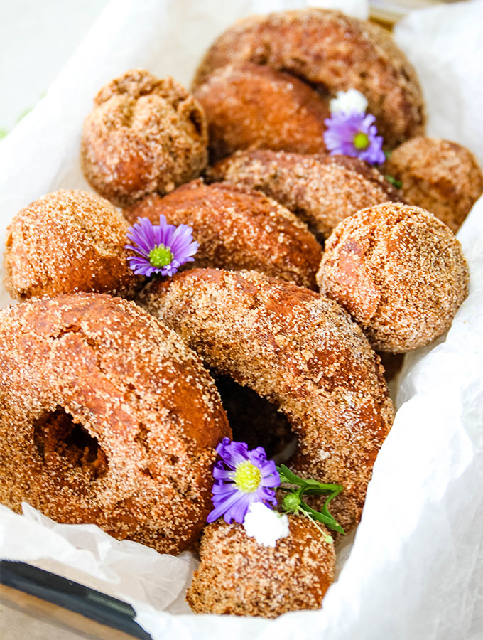 Cider donuts are placed in a parchment paper lined bowl and topped with flowers.