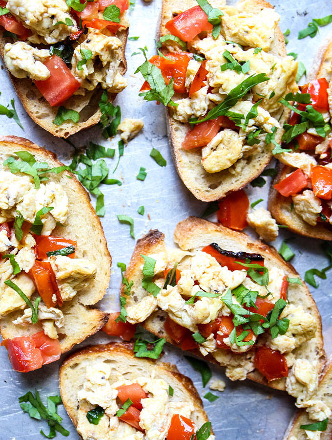 Breakfast bruschetta is placed on olive oil drizzled toast and topped with fresh parsley.