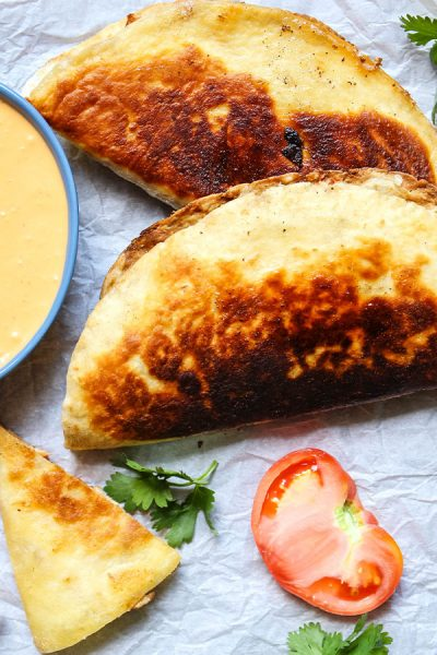 Chicken and cheese quesadillas are plated next to the chipotle sauce on parchment paper.
