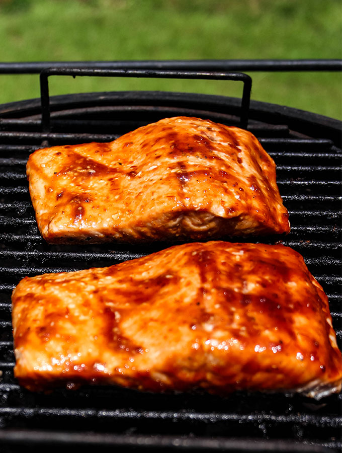 Grilled Bourbon Glazed Salmon is placed on the grill and slathered with BBQ sauce.