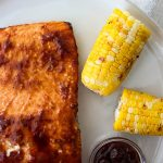 Grilled Bourbon Glazed Salmon is plated with corn and extra bourbon BBQ sauce.
