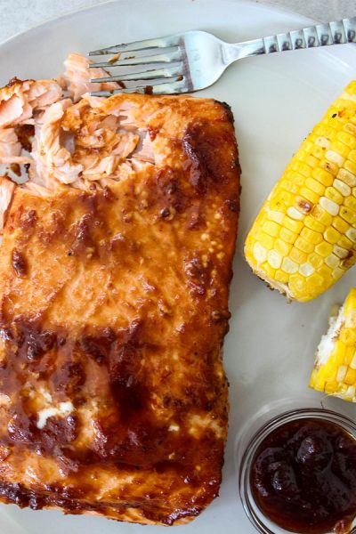 A fork is flaking Grilled Bourbon Glazed Salmon to show texture.