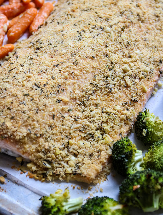 Salmon is baked next to broccoli and carrots on one pan.