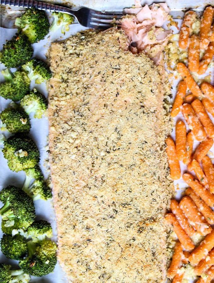 Salmon is laid in between carrots and broccoli on a sheet pan.