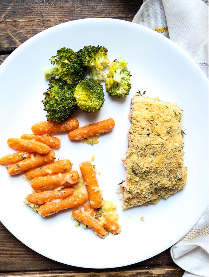 Carrots, broccoli, and a small salmon filet are plated on a white plate.
