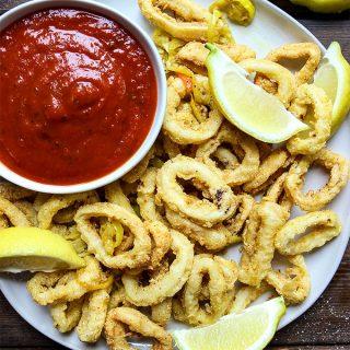 Rhode Island style calamari is plated with marinara sauce and lemon wedges.