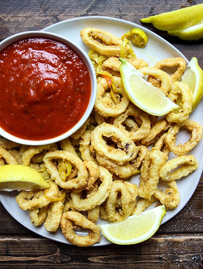 Rhode Island style calamari is plated with marinara sauce and lemon wedges.