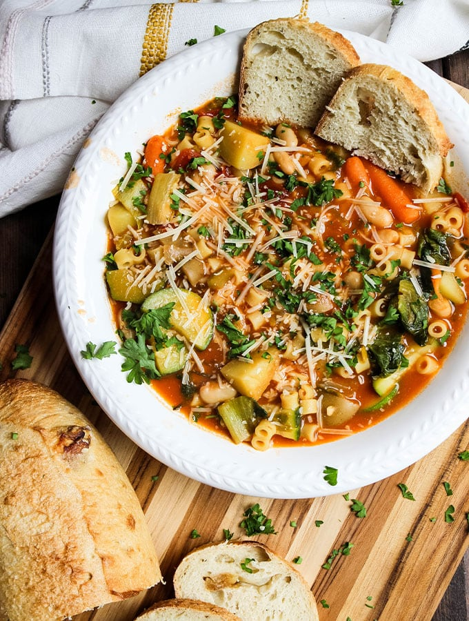 Minestrone soup is plated in a white bowl next to crusty bread and a napkin.