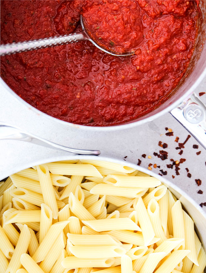 Easy Five Minute Marinara Sauce is placed next to cooked penne pasta.