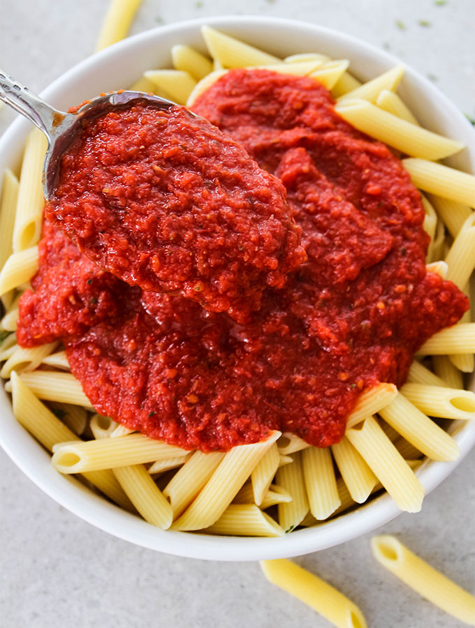Easy Five Minute Marinara Sauce is placed on top of penne pasta.
