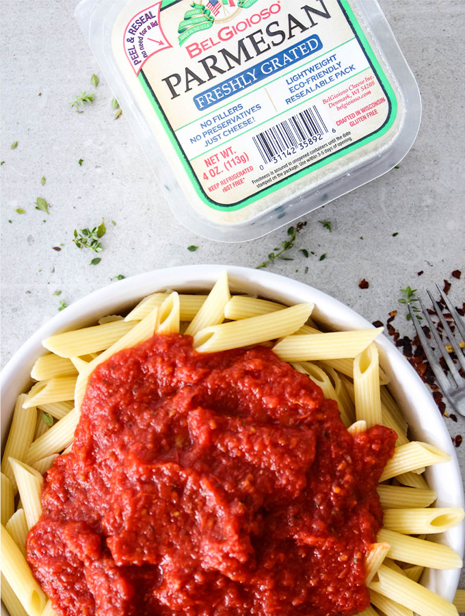 Easy Five Minute Marinara Sauce is placed over cooked penne pasta next to parmesan cheese.