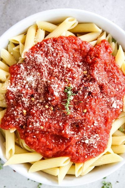 Easy Five Minute Marinara Sauce is placed over penne pasta and topped with parmesan cheese.