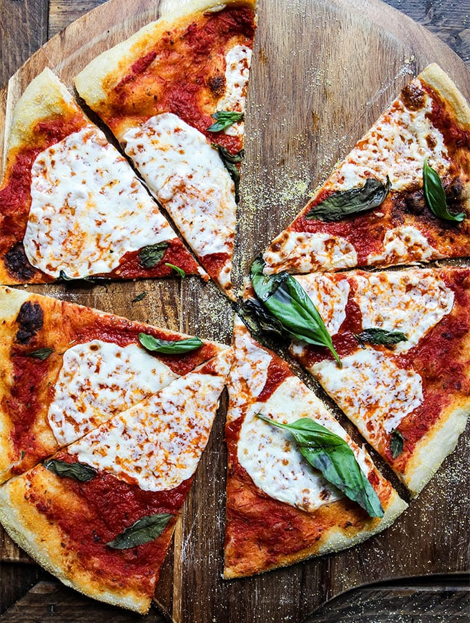 Margherita Pizza is sliced into triangles on a wooden pizza peel.the pizza peel.