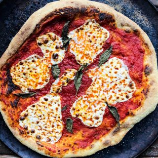 Margherita pizza is cooked on a pizza pan until it is crisped around the edges.