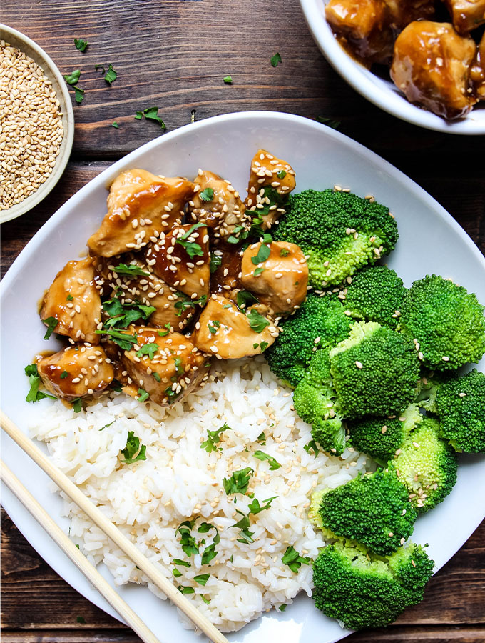 Teriyaki chicken is plated in a white bowl with steamed broccoli and white rice.