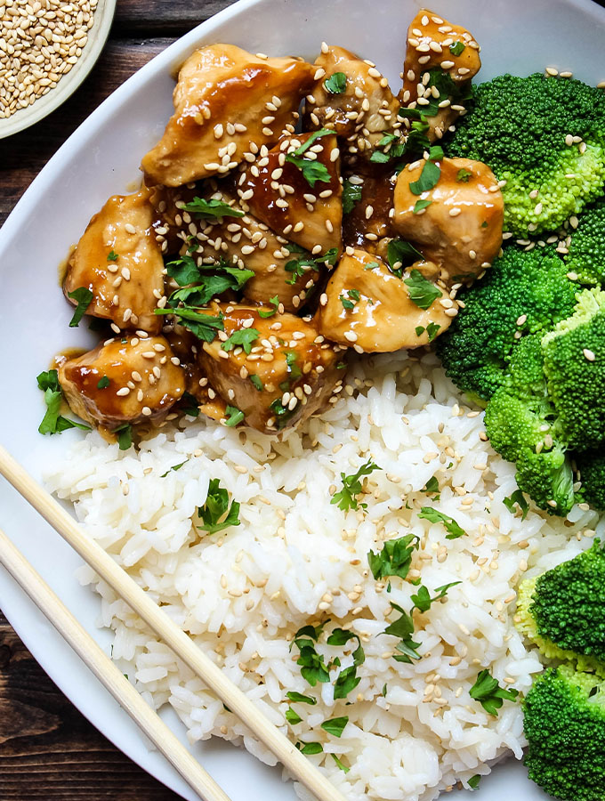 Teriyaki chicken is plated with steamed broccoli and white rice in a white bowl.