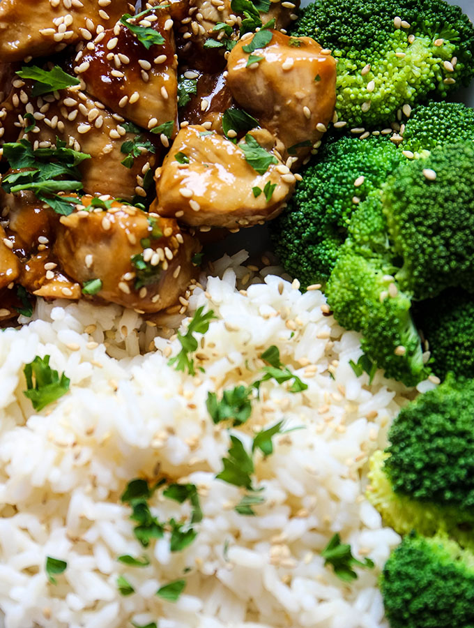 Teriyaki chicken is plated with steamed broccoli and white rice and topped with fresh parsley and sesame seeds.