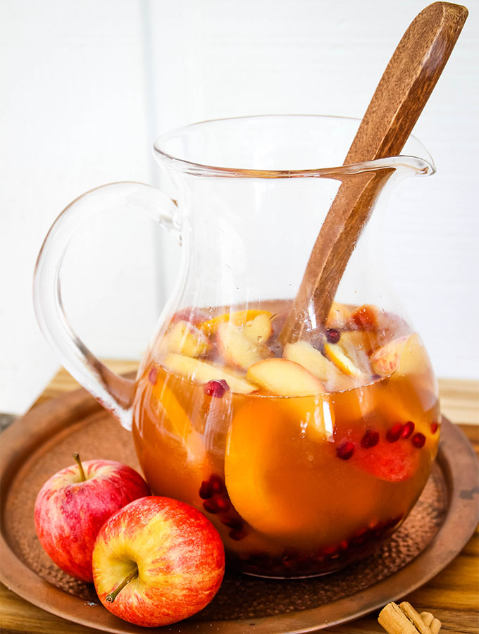 Autumn harvest sangria is made in a large glass pitcher so there is room to stir.