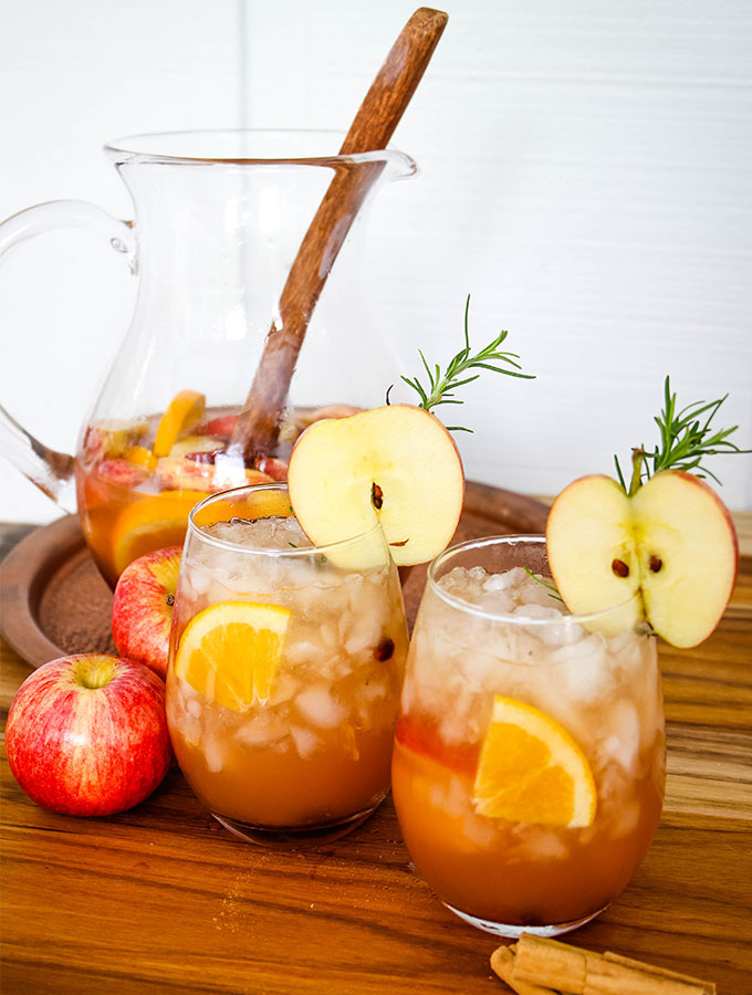 Cups of autumn harvest sangria are poured from the pitcher and topped with apple slices and rosemary sprigs.