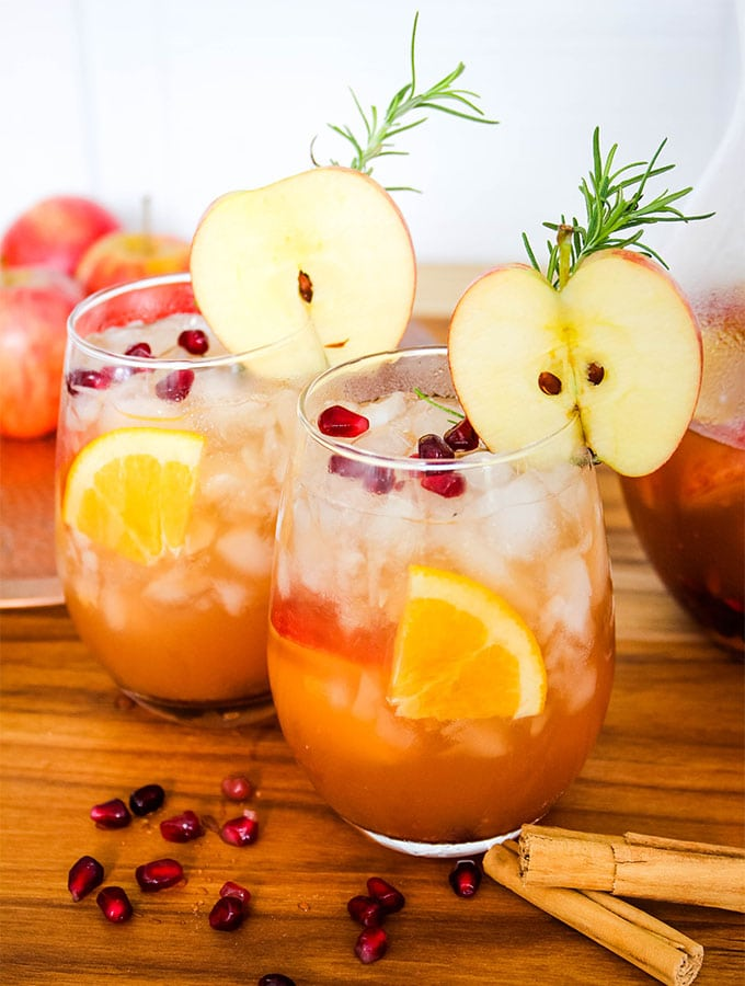Autumn harvest sangria is topped with sliced apples, pomegranate arils, and fresh rosemary for a beautiful drink.