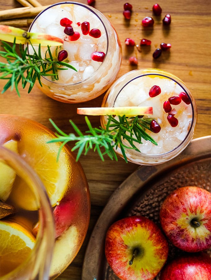 Autumn harvest sangria is poured from the pitcher into glass cups and topped with rosemary and pomegranate arils.