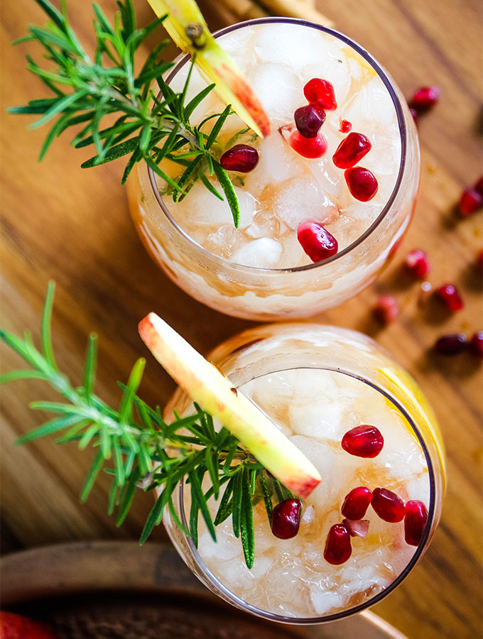 Autumn harvest sangria is poured into individual glasses and topped with fresh rosemary and pomegranate arils.