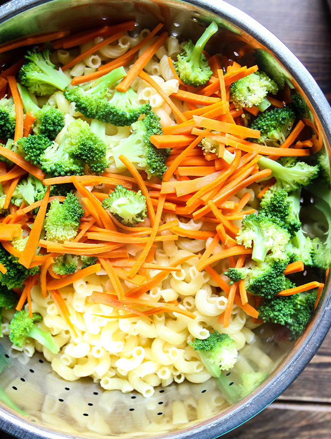 Pasta, broccoli florets, and matchstick carrots are strained in a colander.