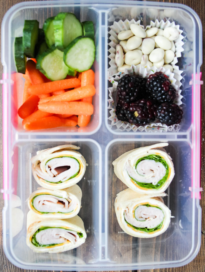 Turkey and ham pinwheels, cucumbers, baby carrots, blackberries, and cranberries are plated in a lunch box.