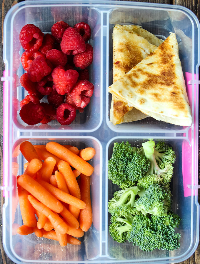 Cheese quesadillas, raspberries, baby carrots, and broccoli florets are plated in a lunch box.