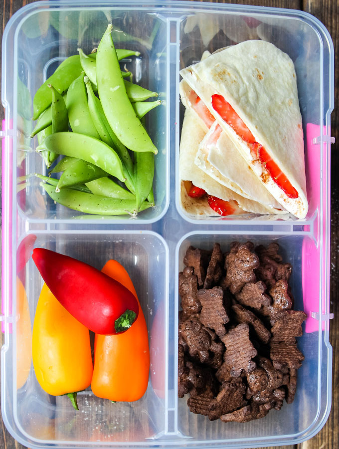 Strawberry tacos, snap peas, snack peppers, and chocolate crackers are plated in a lunch box.